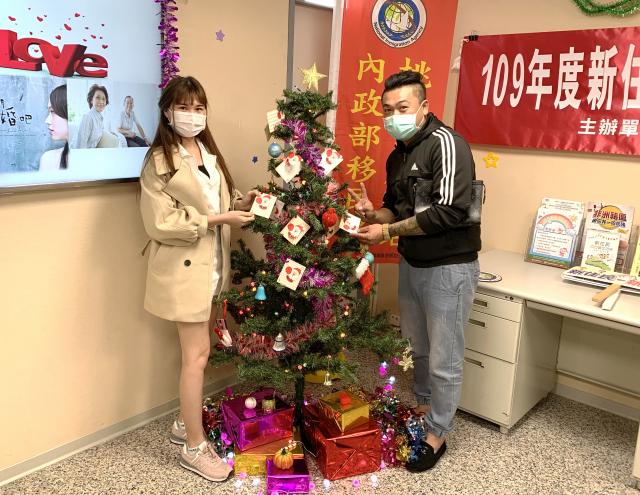新住民夫妻將植愛小卡掛上聖誕樹梢。