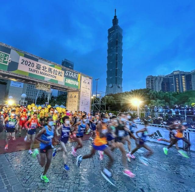 2020臺北馬拉松20日清晨開跑,2萬8千名選手配合防疫規定,戴口罩起跑。(中央社)