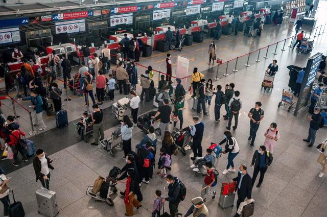 圖為北京首都國際機場的中國民眾。(NICOLAS ASFOURI/AFP via Getty Images)