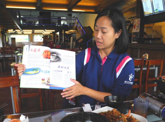 成功農會推廣部主任張慈惠為顧客介紹說菜本上的在地食材。