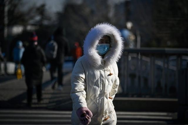1月7日早晨,北京市6個氣象站最低氣溫跌破建站以來歷史極值,最低氣溫達-19.6℃。圖為1月7日北京街上民眾。(WANG ZHAO/AFP via Getty Images)