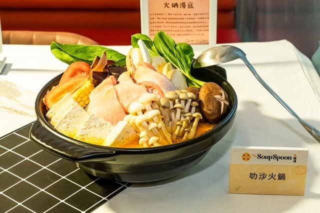 放入高麗菜、金針菇、鴻禧菇、火鍋料、蛤蠣等食材,一鍋溫暖的異國叻沙火鍋即完成。(業者提供)