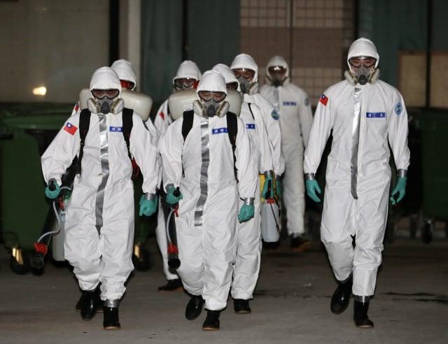 隸屬陸軍第六軍團指揮部的三三化學兵群19日下午前往桃園醫院,全副武裝協助院方加強消毒。(中央社)