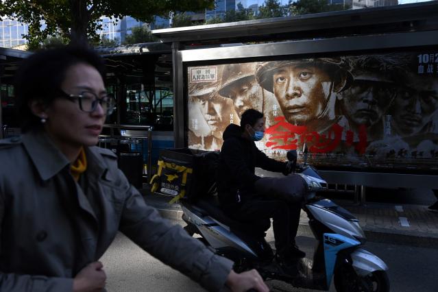 中國2020年票房慘淡,圖為民眾從電影海報前經過。(GREG BAKER/AFP via Getty Images)