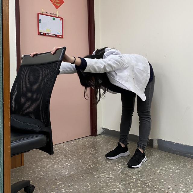 腿部之肌肉伸展與站姿平衡訓練,站姿雙手扶於椅背上,身體向前彎腰。(衛福部八里療養院職能治療科主任張自強提供)