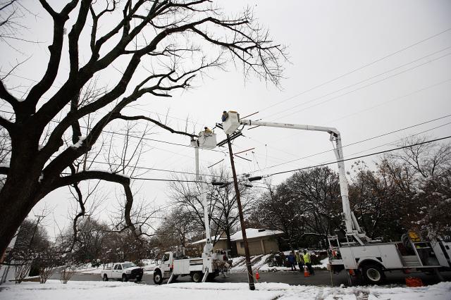 2010年2月12日,工作人員嘗試恢復德州達拉斯市的電力供應,前一夜突然降下超過10英寸的大雪,使該市大部分地區斷電。(Tom Pennington/Getty Images)