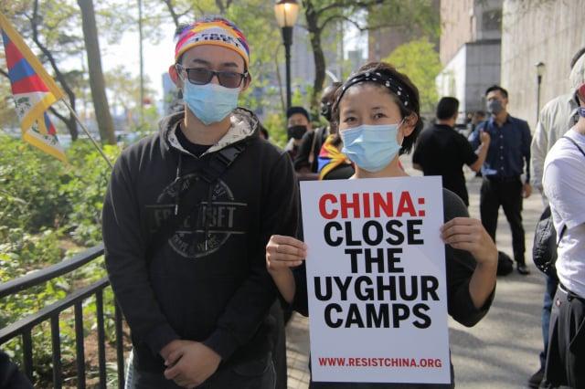 圖為民眾在紐約聯合國總部附近手舉標語要求「中共關閉拘留維吾爾人的集中營」。(黃小堂)