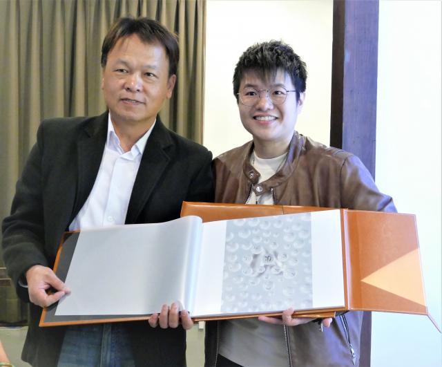3月2日,邱郁淨在臺中文學館的個人攝影展開幕式中,贈送她得獎的攝影作品集予曾能汀副局長。