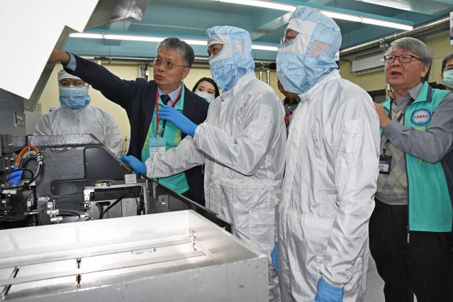 明新科大校長劉國偉(左2.穿西裝者)與來賓一起參觀「半導體封裝測試工程師能力鑑定」試場。