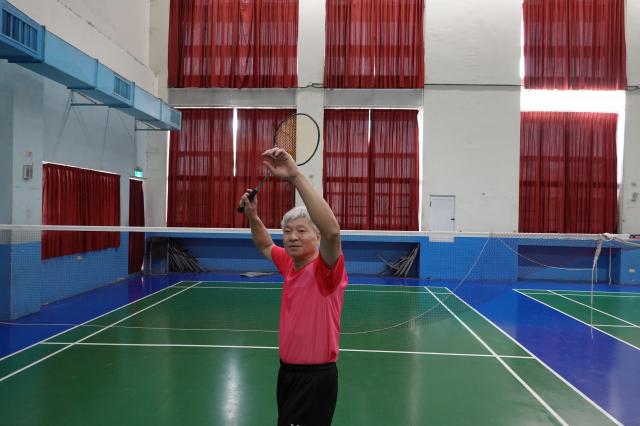 和睦國小羽球隊教練洪清忠持羽球拍英姿。