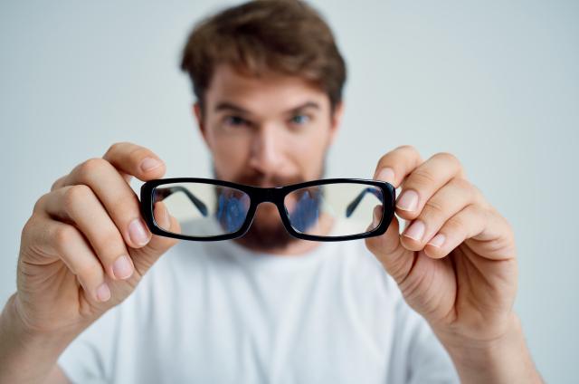 取戴眼鏡要雙手持拿,才能避免鏡框、鏡腳變形。(Shutterstock)