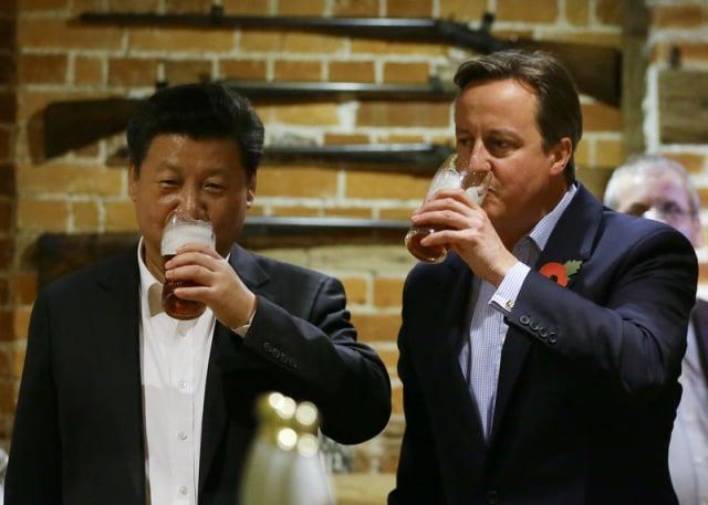 2015年10月22日,時任英國首相卡麥隆(右)和中國國家主席習近平(左)在鄉村酒吧喝酒。(Kirsty Wigglesworth - WPA Pool/Getty Images)