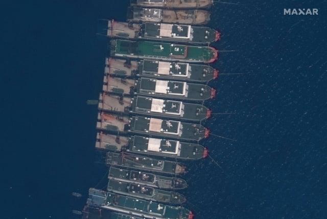 中共近期在南海爭議海域集結船隻,引發菲律賓強烈抗議。圖為3月23日集結在牛軛礁附近的中國船隻。(Handout/Satellite image ©2021 Maxar Technologies/AFP)