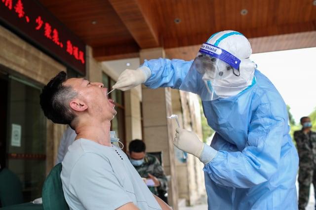 自瑞麗市新任市委書記翟玉龍4月8日上任後,當地的抗疫措施更加嚴苛。圖為瑞麗市民接受檢測。(STR/AFP via Getty Images)