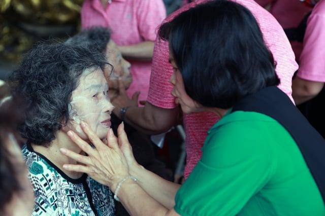 年輕的媽媽為阿嬤敷面膜。
