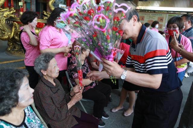 四結福德廟主任委員高志肇逐一發送康乃馨給婆婆、媽媽們。