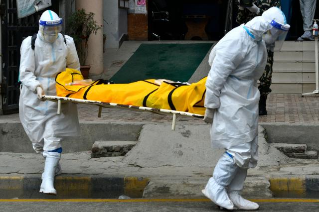 2021年5月5日,身穿個人防護用品(PPE)的尼泊爾陸軍人員將一名中共病毒患者屍體送往加德滿都火葬場。(PRAKASH MATHEMA/AFP via Getty Images)