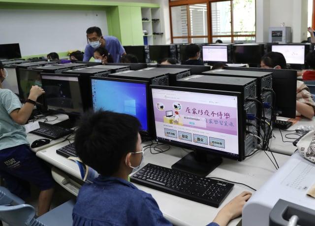 校方趕在放學前讓學生熟悉居家學習的方式。 (中央社)