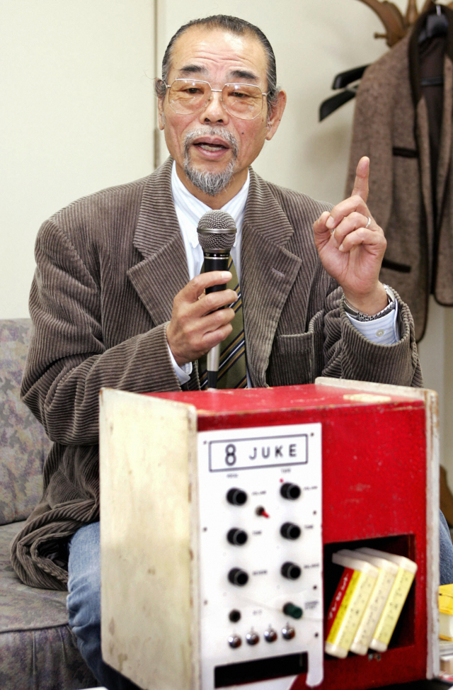 2004年11月9日,井上大佑在位於日本西宮市的辦公室展示他發明的世界首款卡拉OK機。(YOSHIKAZU TSUNO/AFP via Getty Images)