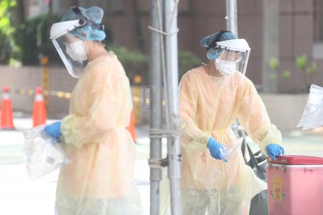 圖為醫護人員在篩檢站將檢體蒐集保存。(中央社)