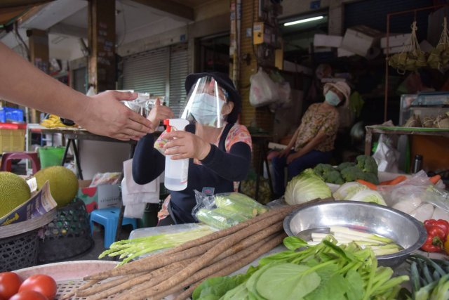 為避免傳統市場成為防疫破口,屏東縣政府派員在曾有確診足跡熱區的屏東、內埔、潮州、東港的傳統市場發放防護面罩。(屏東縣政府提供)
