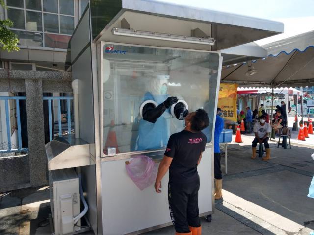 屏東縣設置東港外籍船員PCR篩檢站,讓目前滯留在港超過200位外籍船員全面篩檢,12日已篩檢39位外籍船員。(屏東縣政府提供)