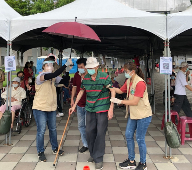 屏東縣大規模疫苗施打首日,社工員在下車處為長者撐傘,協助快速通關,讓家屬和長輩都備感親切。
