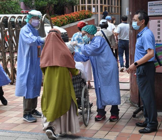 北市建成國中疫苗接種站16日上午開放施打,醫護人員在門口為民眾測量體溫與消毒雙手。(中央社)