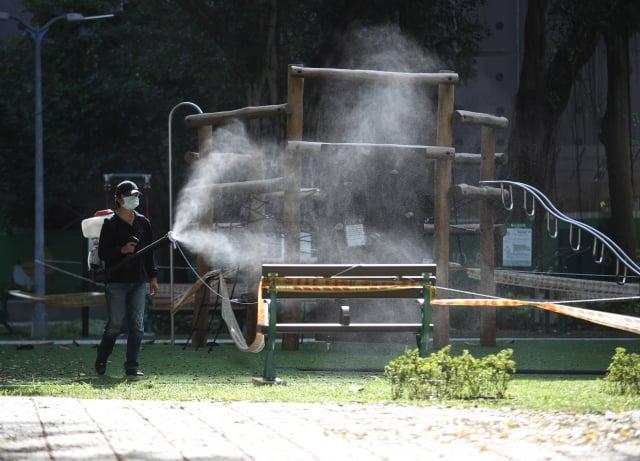 清潔公司人員協助消毒周遭環境。 (中央社)