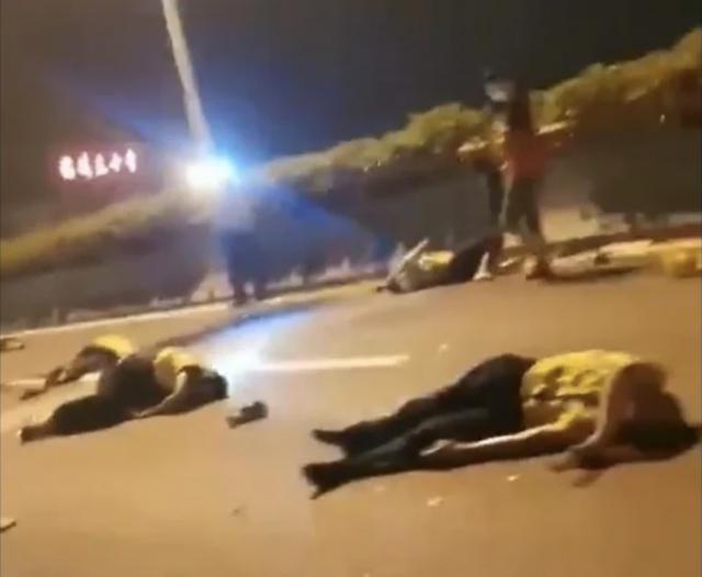 網友拍攝到身著交警制服的人橫七豎八的倒在快速道路上。(網路影片擷圖)