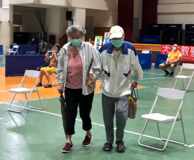 高市福誠高中接種站有一對牽手老夫妻,85歲阿公已打過疫苗,再特地陪阿嬤施打。(高市府提供)