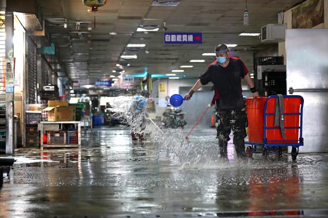 圖為第二果菜批發市場21日休市,安排清潔人員進行清消。(中央社)