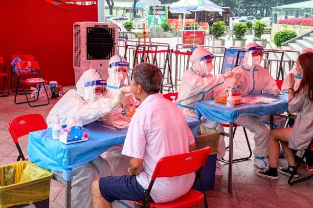 廣東官方稱要興建健康驛站代替隔離酒店,讓民眾質疑疫情根本沒受控制。圖為民眾接受篩檢。(STR/AFP via Getty Images)