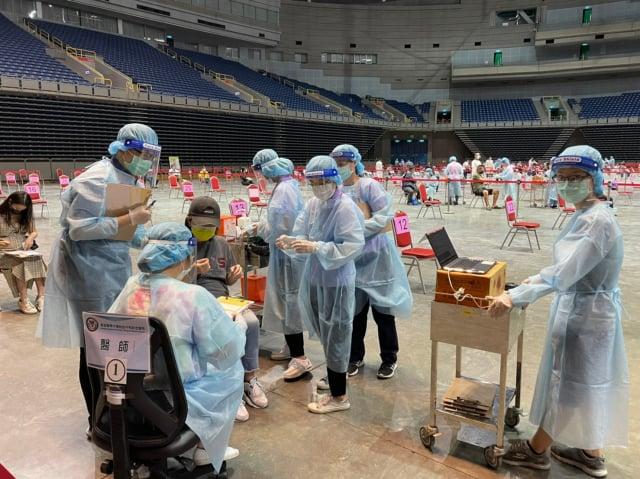 高雄醫學大學醫學生全副武裝協助民眾施打疫苗。(高醫提供)