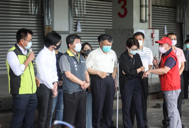 環南市場疫情嚴峻,指揮中心指揮 官陳時中(左3)與臺北市長柯文哲(左4)2日上午到場了解狀況。(中央社)