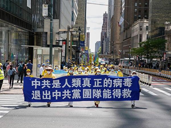 2021年5月13日,紐約部分法輪功學員在曼哈頓舉行遊行,他們在隊伍中拉起「中共是人類真正的病毒 退出中共黨團隊能得救」橫幅。(記者張靜怡/攝影)