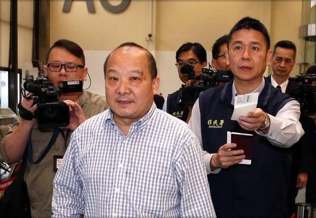 圖為2019年4月12日,李毅被臺灣移民署人員押送出境。(中央社)