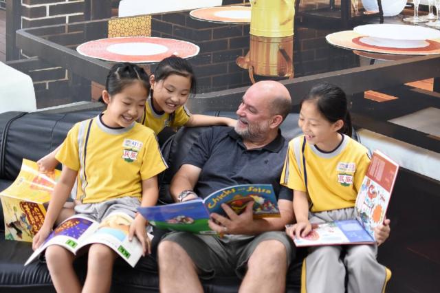 外籍教師與學生共讀英語圖書(資料照)。