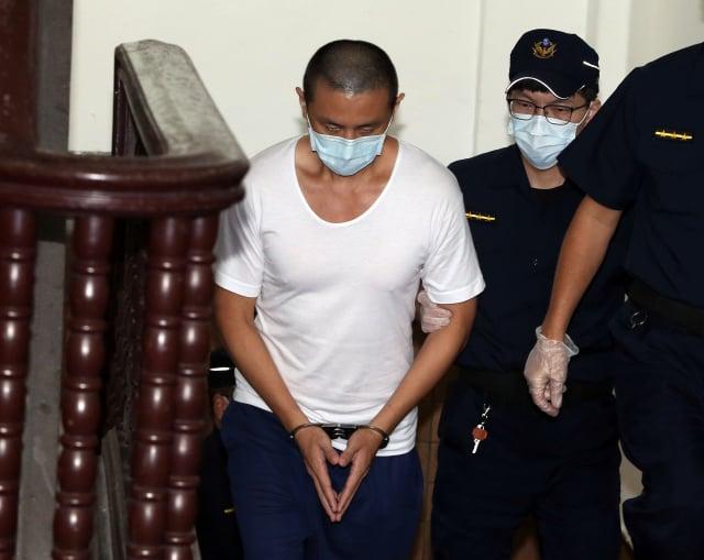 梁姓男子被控砍下母親頭顱從12樓拋下,一度無罪遭撤銷,臺灣高等法院更一審14日宣判,判他無期徒刑。圖為梁男(左)14日提訊出庭。(中央社)