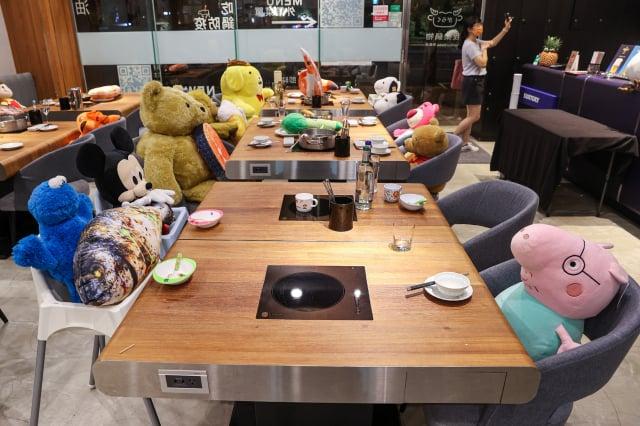 有餐廳業者苦中作樂,在內用座位上擺滿玩偶。(中央社)