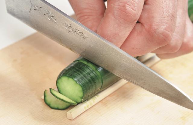 將小黃瓜擺在2根筷子之間,從邊端開始劃入切口。每一次下刀, 都要切達筷子處。盡可能劃得越細越好。(愛米粒提供)
