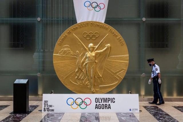 2020年東京奧運會因為疫情延後一年後,7月23日晚上將舉行開幕式。圖為7月20日,警衛走過奧運金牌雕塑。(Yuichi Yamazaki/Getty Images)