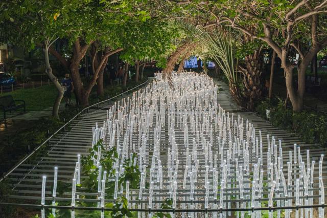 由香港「WHITEGROUND」團隊打造的「The Wishing Field光圳」,由3千條LED燈管組成,與下方隆恩圳水道波浪相輝映,當風吹過時,光源還會隨之調整,在漆黑間閃爍、遠望過去宛如整片絕美稻浪。(竹市府提供)