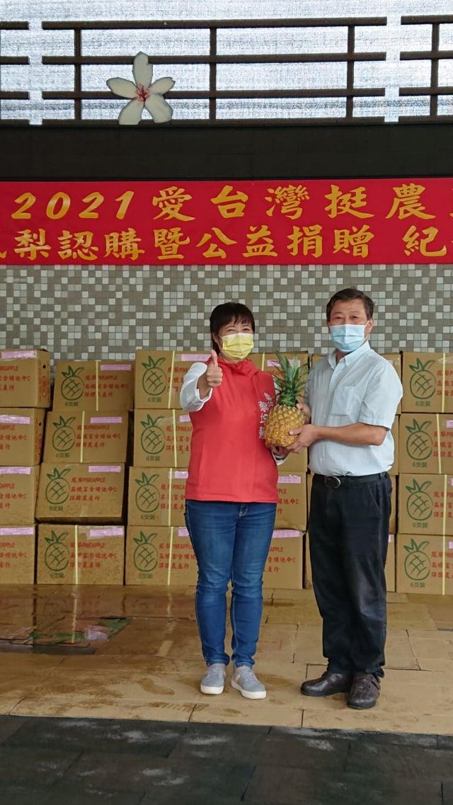 國姓丘埔生(右)代表國姓鄉親接受萬斤鳳梨的捐贈,並感謝行政院中服中心執行長蔡培慧(左)的牽線。