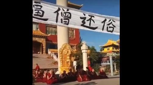 紅城寺遭當地政府強行關閉,僧人遭暴力驅趕,拉橫幅抗議。(網路影片擷圖)