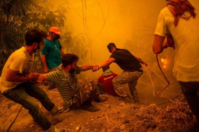 8月8日,希臘第二大島艾維亞野火失控,居民協助打火。(ANGELOS TZORTZINIS/AFP via Getty Images)