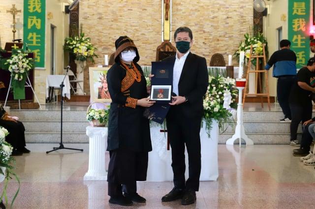 文化部長李永得(右)親赴《斯卡羅》演員查馬克.法拉屋樂追思儀式致意,追頒三等文化獎章。(文化部提供)