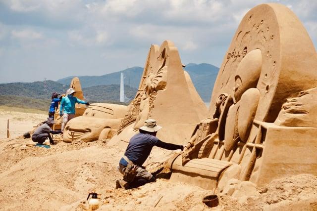 沙雕師從夯沙模板到塑型,不論風吹雨打,皆有人駐點以人工方式進行修補維護。(福容大飯店提供)