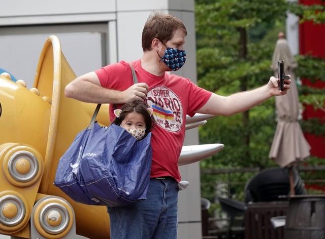 圖為一名家長用購物袋背著幼童拍照。(中央社)