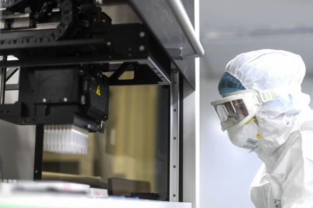 中國企業華大推出的基因產檢產品,因隱私問題受到各國質疑。圖為華大工作人員。(STR/AFP)